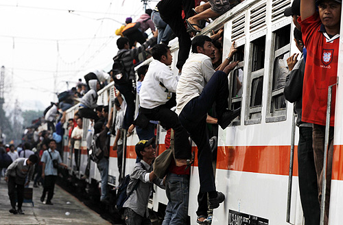 People climb up to the top of the roof of a train heading to their homes after work in Jakarta.