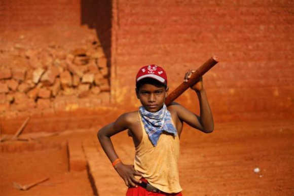 Mithun, 11, poses for a photo at a laterite brick mine in Ratnagiri district, about 360km south of Mumbai. He is paid Rs 2 per brick and carries an average of 100 bricks out of the mine per day. Each brick costs between Rs 10-14, and weighs around 40kg.