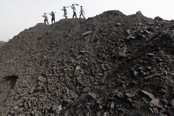 Workers walk on a heap of coal at a stockyard of an underground coal mine in the Mahanadi coal fields at Dera near Talcher town in Orissa.