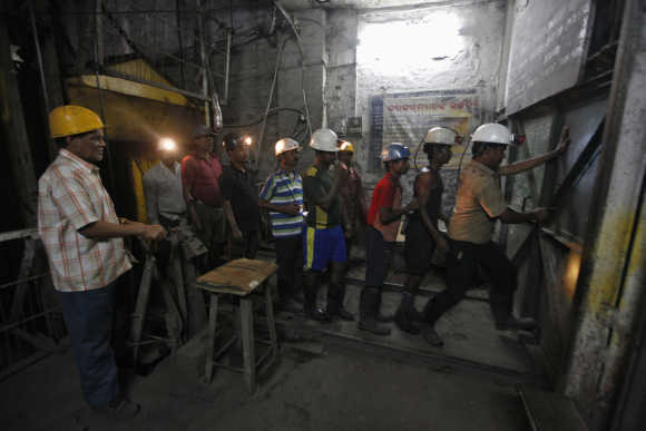 A worker opens the entry gate of an underground coal mine in the Mahanadi coal fields at Dera near Talcher town in Orissa.
