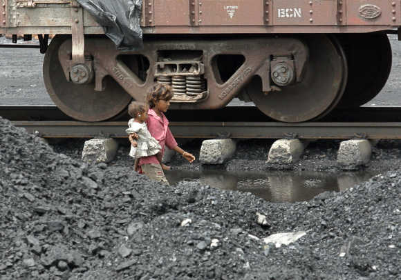 Children of labourers walk beside a railway track on the outskirts of Ahmedabad.