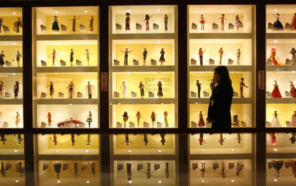 A curator walks past displays of Barbie dolls at the Doll Industry Museum in Taishan, Taipei County.