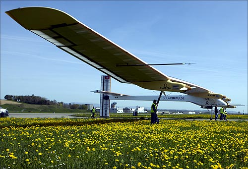 Staff push the Solar Impulse's solar-powered HB-SIA prototype airplane after a test flight at Payerne airport.