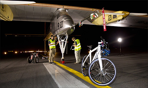 Crew members check the Solar Impulse plane.