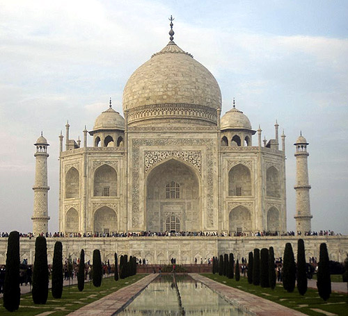 Tourists stand in front of the historic Taj Mahal