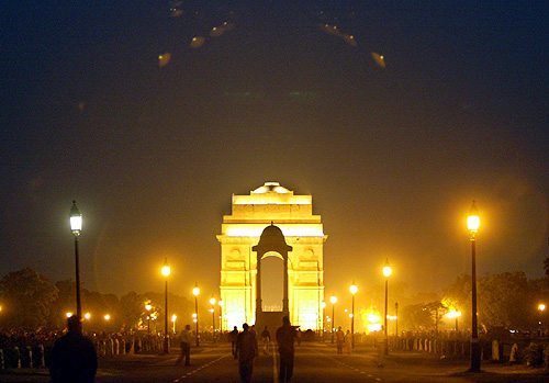 People walk near the historic India Gate on a hot evening in New Delhi.