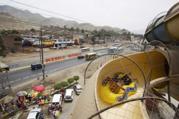 A boy slides down with a float at a big water slide at a water park in Lima.
