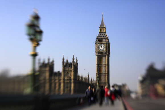 Pedestrians walk across Westminster Bridge in front of the Big Ben Clock Tower in London.