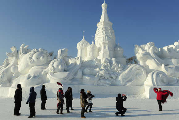 Tourists take pictures in front of a snow sculpture in Harbin, Heilongjiang province, China.