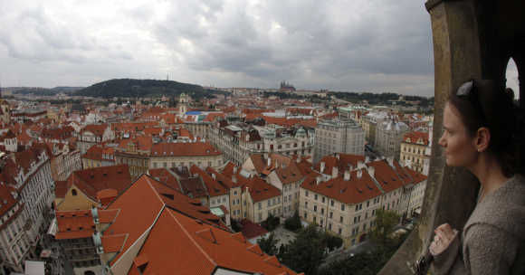 A tourist looks at Czech capital Prague from Old Town Hall Tower at historical Old Town Square.