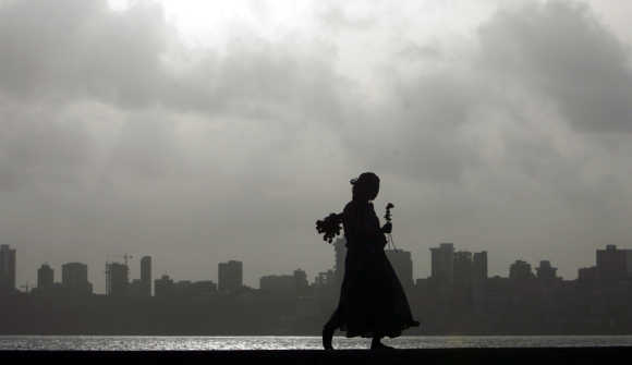 A flower seller looks for possible buyers at a seafront in Mumbai.