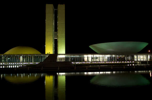 The National Congress building in Brasilia is illuminated with green and yellow lights.