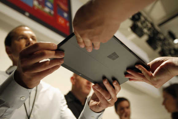 Microsoft representative hands the Surface tablet to a member of the press in Los Angeles, California.
