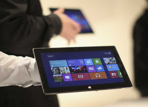 Microsoft representatives hold the Surface tablet computer as it is unveiled in Los Angeles.