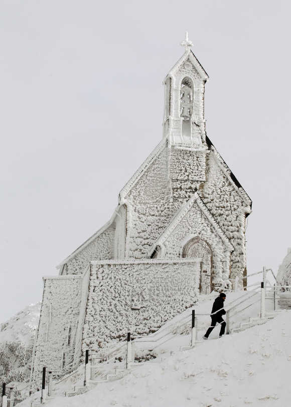 A man walks below a frost covered Wendelstein church, Germany's highest church, on the 1,838 metres (6,030 feet) high Wendelstein mountain near Bayrischzell.