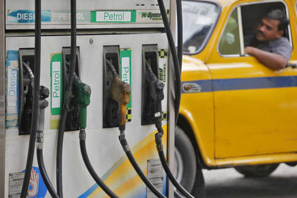 A driver waits in a taxi for his turn to fill up his tank with diesel at a fuel station in Kolkata.