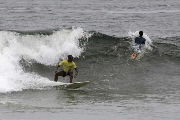 Competitors ride waves at the third annual Surf Liberia Contest at Robertsport on the coast of the West African nation.