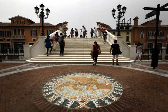A Venetian Lion emblem adorns the footpath as pedestrians walk across a bridge over a canal that flows through the centre of the Florentia Village in Wuqing, Tianjin, China.