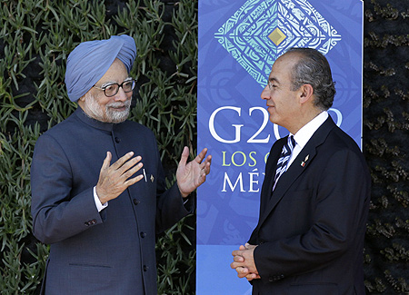 Prime Minister Manmohan Singh (L) is welcomed by Mexican President Felipe Calderon to the G20 Summit in Los Cabos.