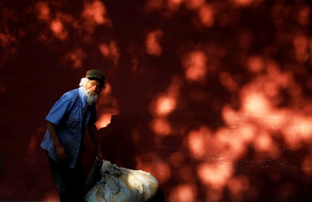 A homeless man lifts his belongings in front of a wall surrounding the Forbidden City in central Beijing.