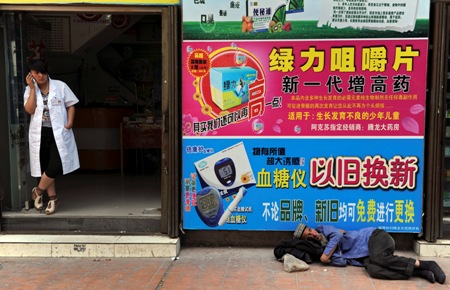 Ethnic Uighur man sleeps in front of posters advertising medical products as an employee talks on her mobile phone at the entrance of a pharmacy in Aksu.