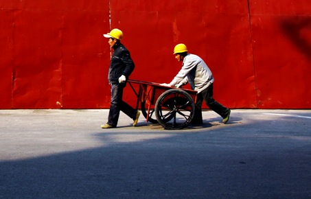 Migrant workers move a cart down a road near a construction site in Beijing.