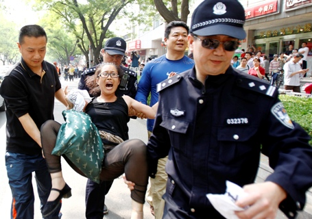 Police carry away a woman who started a protest for personal economic reasons in front of the media outside Chaoyang Hospital in Beijing.