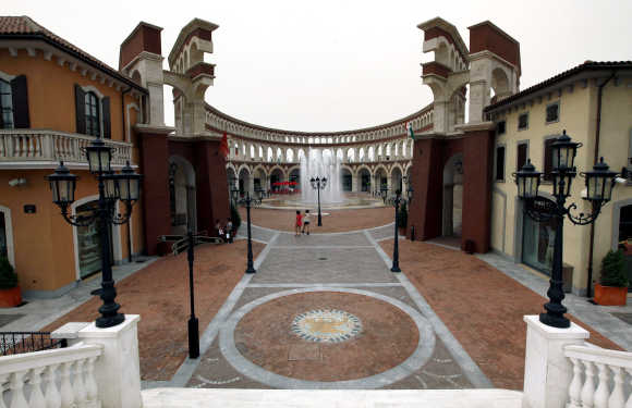 Two women walk through a building that resembles a Roman Coliseum at the Florentia Village in Wuqing, Tianjin, China.