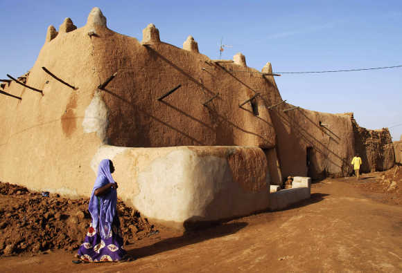 A Tuareg woman crosses the street in front of a mud building in the Old Quarter of the desert city of Agadez.