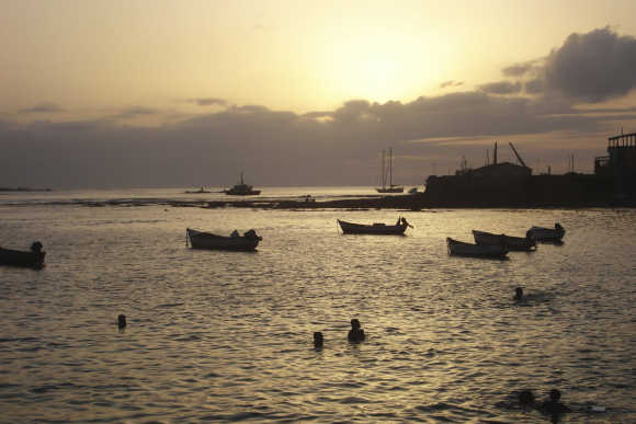 Children play in the water at sunset in the port of Sal Rei in Cape Verde.