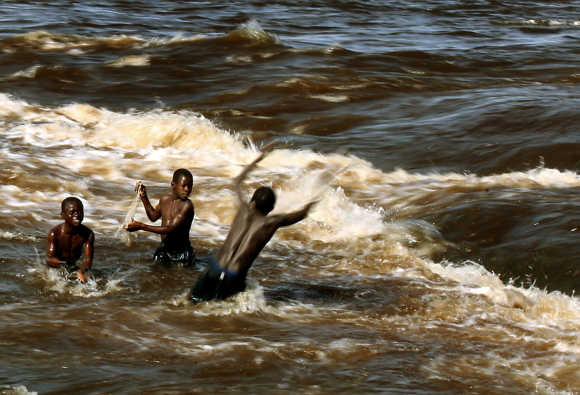 Boys throw fishing net in Congo River on outskirts of the capital Kinshasa.