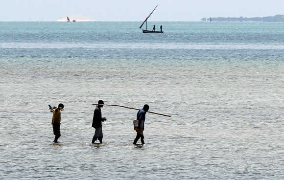 Local fishermen walk to a fishing boat on the Indian Ocean shore line in Vilanculo, Mozambique.