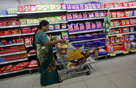 A woman fills her trolley with retail products as she shops at a Hypercity department store.