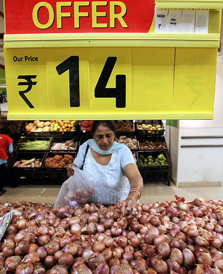 A woman selects onions in the fresh foods section of a Reliance Fresh supermarket in Mumbai.