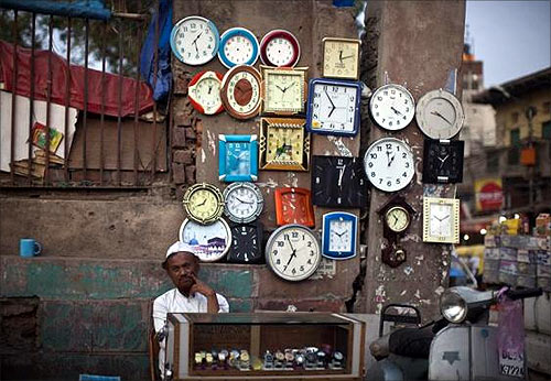 A roadside vendor waits for customers at his stall of clocks and watches in the old quarters of Delhi.