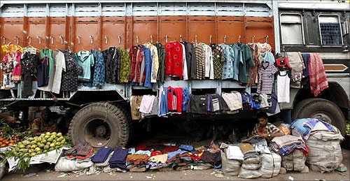 Vendors selling fruits and clothes wait for customers at their stalls under a parked truck, on a roadside in Kolkata.
