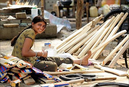 A woman adds finishing touches to cricket bats being made along a roadside in Nagpur.