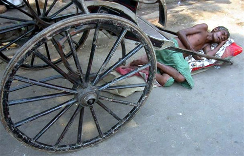 A hand rickshaw puller rests on a pavement in Kolkata.