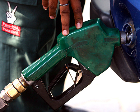 A worker fills a car with fuel at a petrol station in New Delhi.