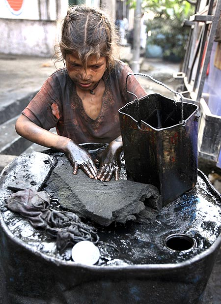 Eight-year-old Gudia, an oil scavenger, collects engine oil at an auto workshop in Jammu.