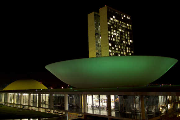 National Congress building in Brasilia is illuminated with green and yellow lights.