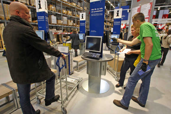 Customers check products on computer terminals at Ikea's store in Malmo, Sweden.
