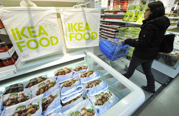 A shopper walks past food refrigerator and Ikea branded bags at Wembley branch in west London.