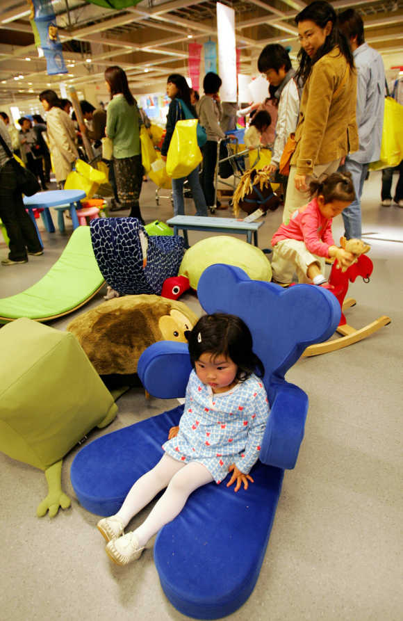 A girl rests on Ikea's teddy bear shaped chair at the company's store in Japan in Funabashi, east of Tokyo.