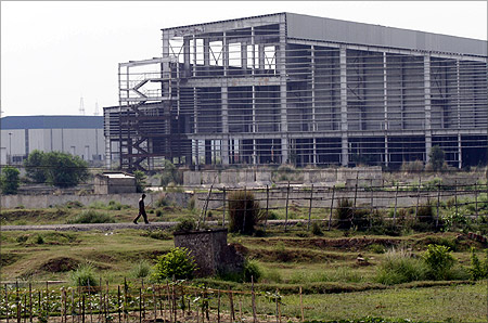 A private security guard walks outside the closed Tata Motors Nano car factory in Singur, north of Kolkata.