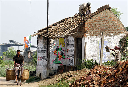 man rides his bicycle as farmers repair the roof of a house near a closed Tata Motors Nano car factory in Singur.