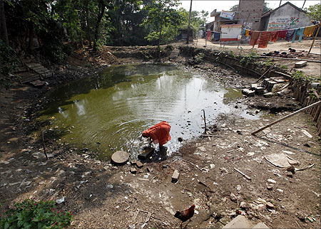 A woman washes her utensils in a polluted pond at Singur, north of Kolkata.