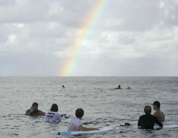 Surfers look at a rainbow in Teahupoo, Tahiti.