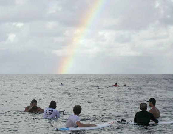 Surfers look at a rainbow in Teahupoo, Tahiti.