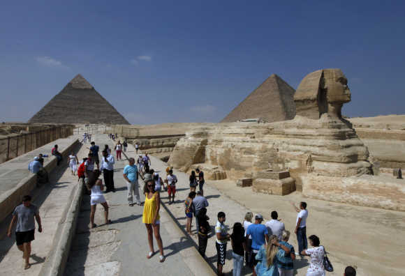 Tourists take pictures at the Sphinx and the Pyramids of Giza in Cairo.